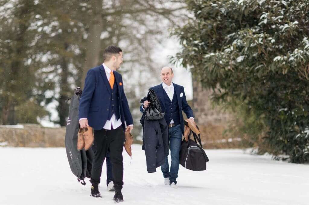 002 groom groomsmen trudge through winter snow berkeley castle stately home gloucestershire oxfordhire wedding photography