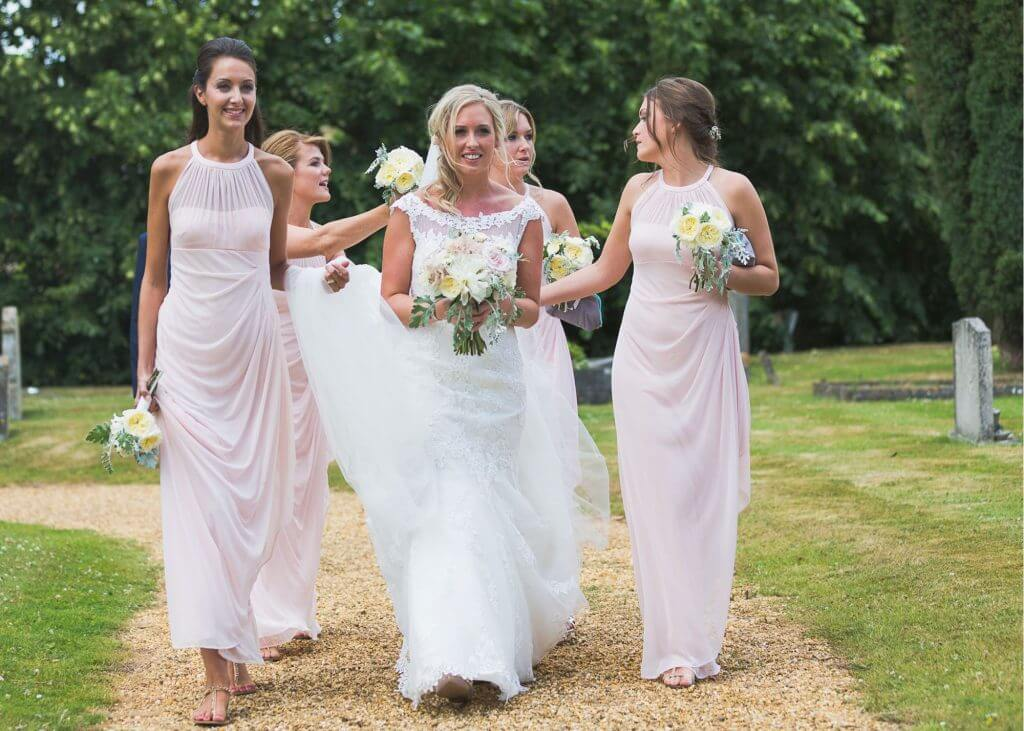 01 bride bridesmaid walk through churchyard to church marrage ceremony oxfordshire wedding photographer