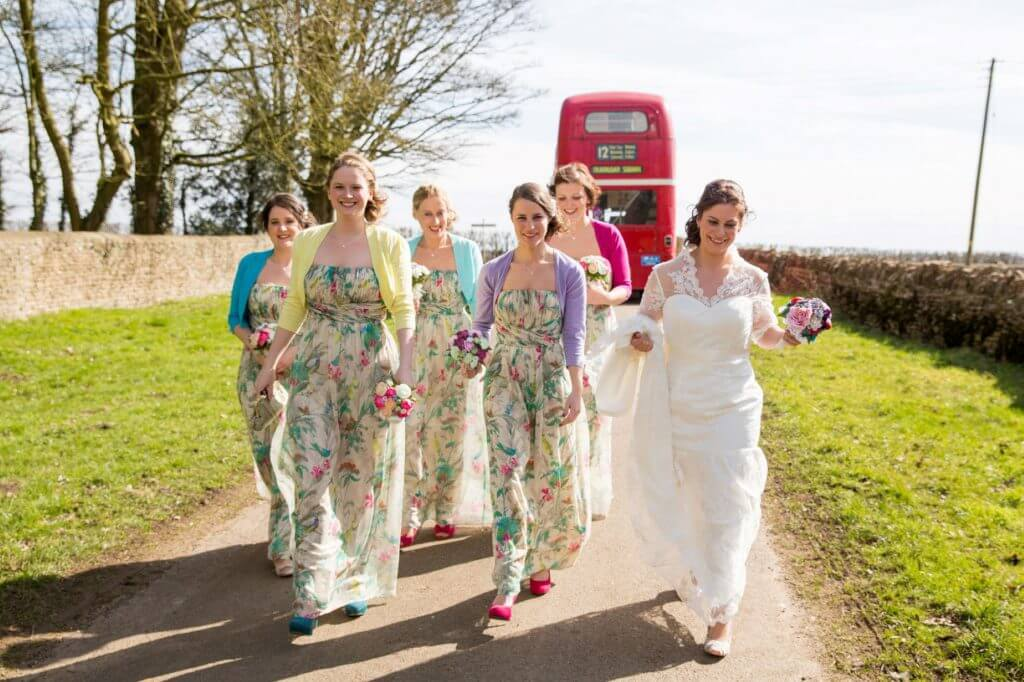 02 bride bridesmaids colourful dresses red double decker bus walking to church marriage ceremony oxfordshire wedding photography