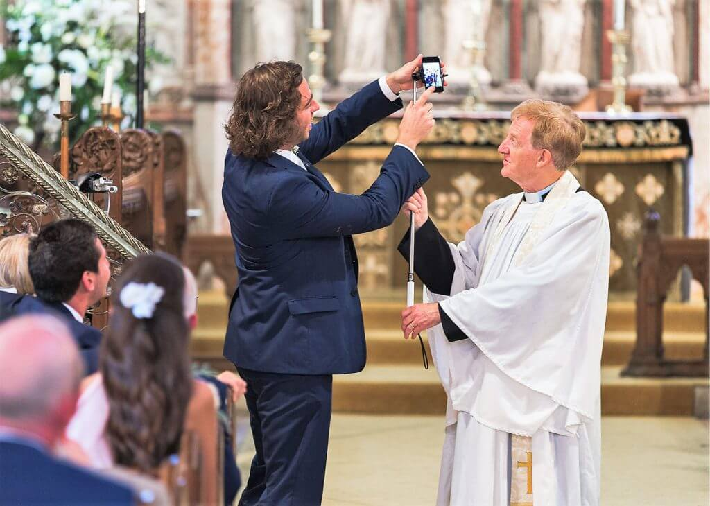 02 guest shows vicar selfie stick at church marriage ceremony oxfordshire wedding photography