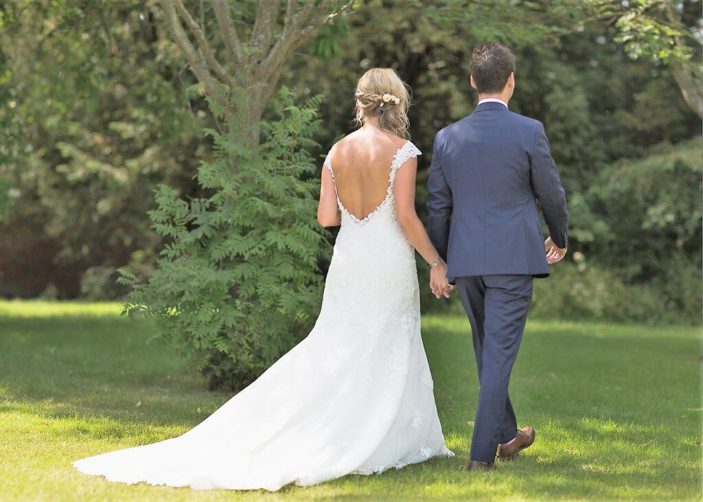 05 bride long flowing open back dress and groom stroll alone at garden reception venue oxford wedding photographer