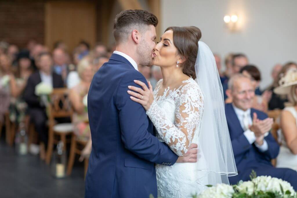 08 bride groom first kiss marriage ceremony mythe barn luxury venue leicestershire oxford wedding photography