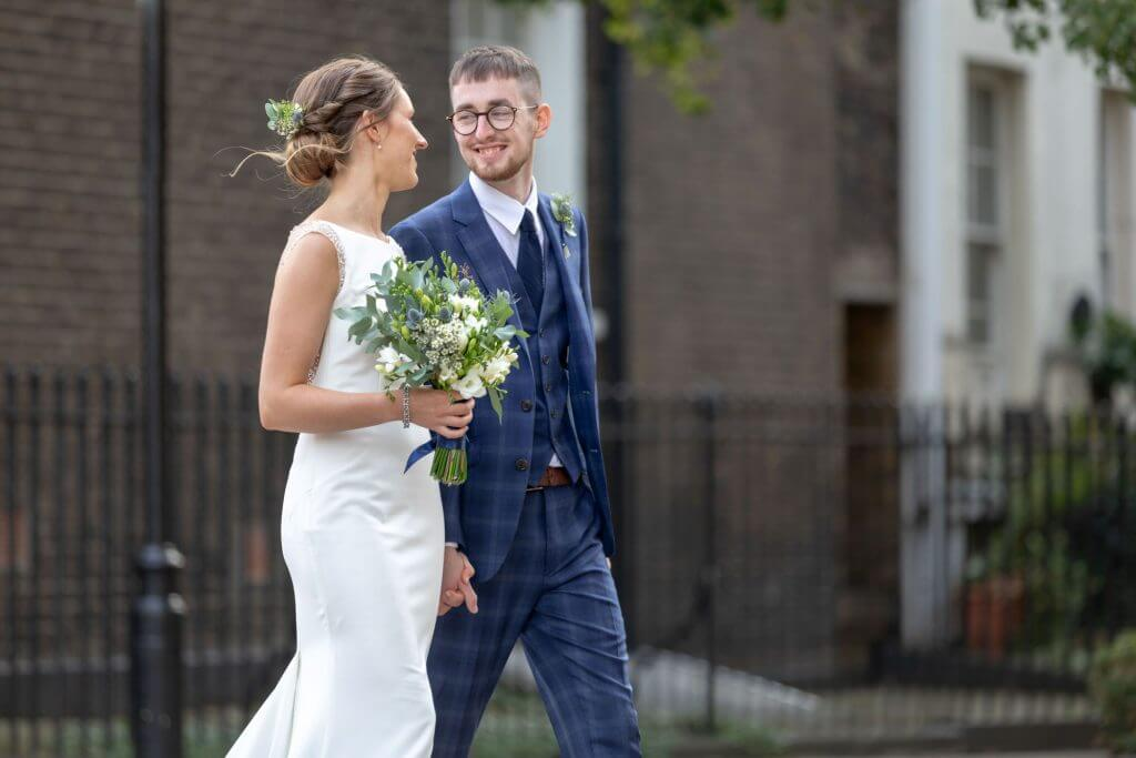 08 happy bride with floral bouquet holds hands with groom st marys church bryanston square marylebone london oxfordshire wedding photographer