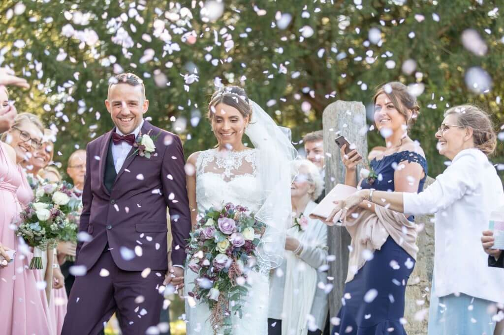 09 bride groom showered with confetti churchyard iffley village church oxford oxfordshire wedding photography