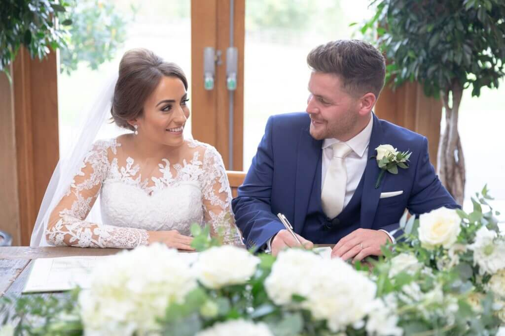 09 bride groom signing register after marriage ceremony mythe barn luxury venue leicestershire oxfordshire wedding photography