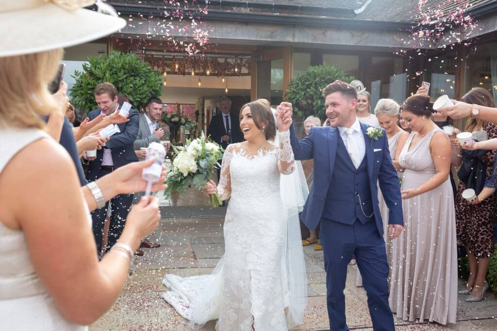 11 happy bride groom guests throw confetti mythe barn luxury venue leicestershire oxfordshire wedding photography