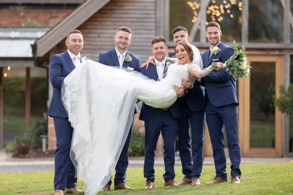 12 groom groomsmen carry bride with bouquet mythe barn luxury venue leicestershire oxford wedding photography