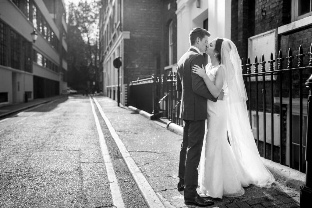 15 bride white dress long veil and groom kiss in clerkenwell street after marriage ceremony museum of the order of st john london oxfordshire wedding photography