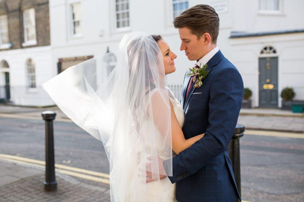 16 bride flowing veil and groom embrace in clerkenwell street after marriage service museum of the order of st johns london oxfordshire wedding photography