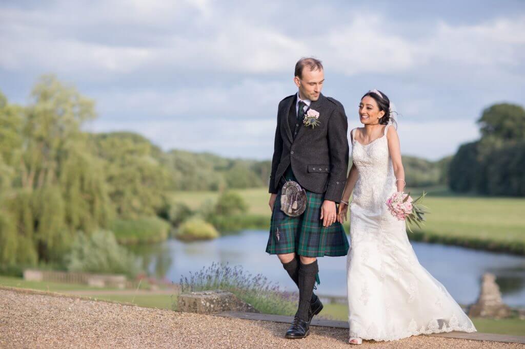 19 bride groom stroll by river at stoneleigh abbey kenilworth warwickshire oxfordshire wedding photography