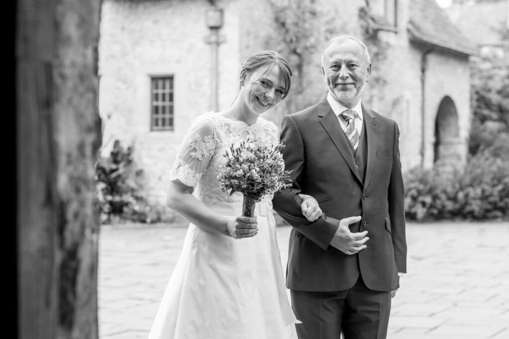 19 father of the bride with daughter holding flowers bouquet entering church for marriage ceremony oxfordshire wedding photography