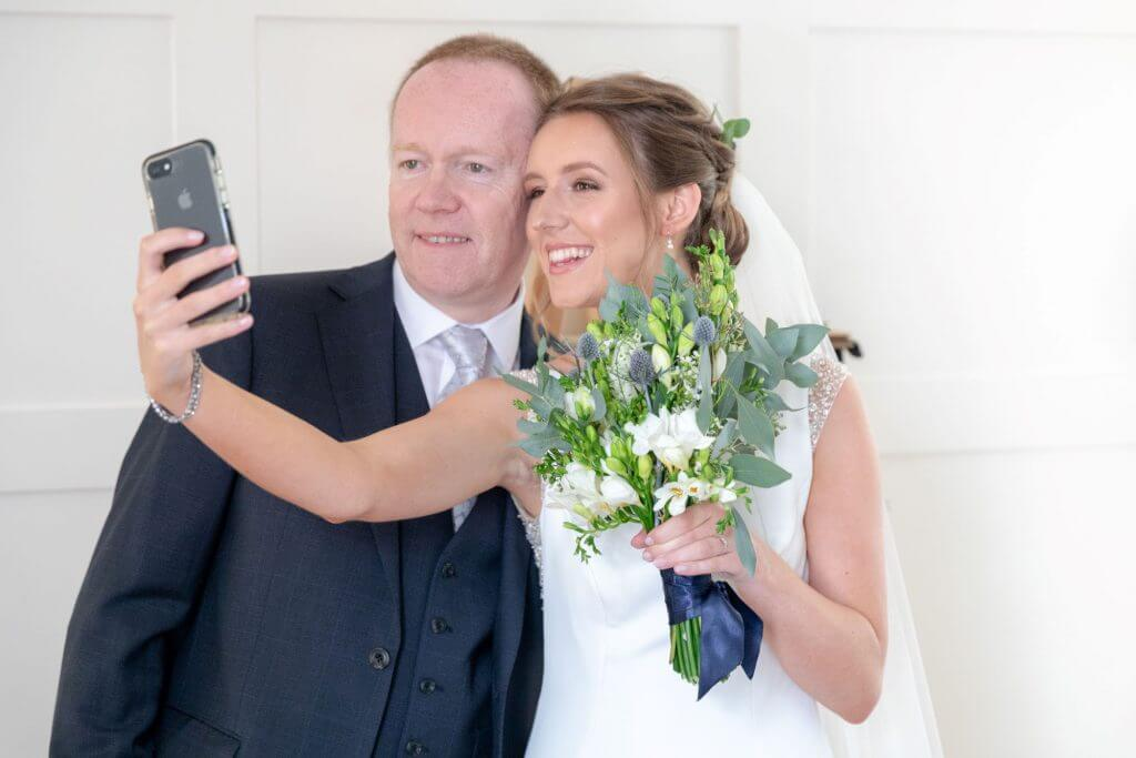 22 father of the bride with daughter holding flowers bouquet taking selfie st marys church bryanston square marylebone london venue oxfordshire wedding photography