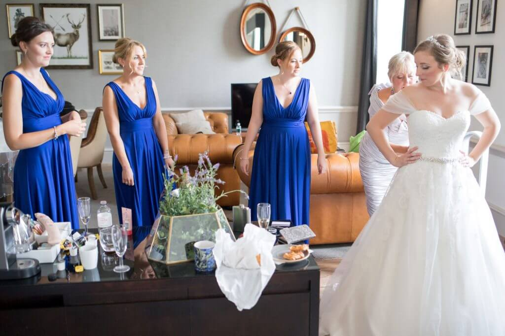 23 mother of the bride and bridesmaids help with dress bridal preparation de vere beaumont estate venue windsor berkshire oxford wedding photographer