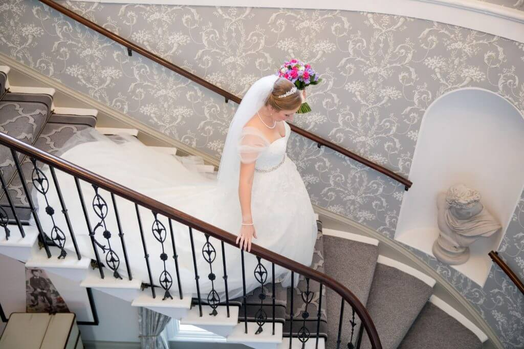 26 bride long flowing white dress on staircase de vere beaumont estate venue windsor berkshire oxford wedding photographer