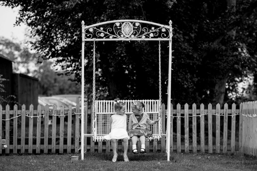 27 two young girl guests on garden swing celebration reception buckinghamshire venue oxfordshire wedding photography