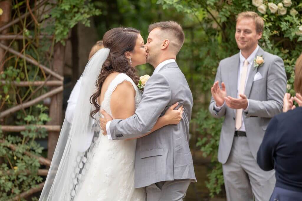 29 bride groom first kiss summer garden marriage ceremony oxforshire wedding photographer