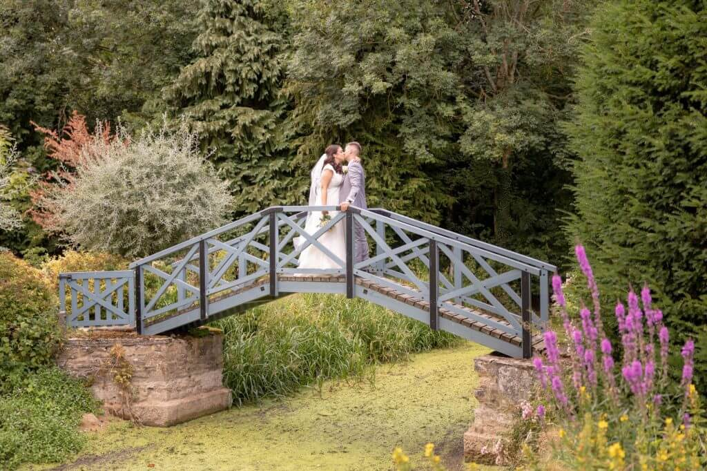 35 bride groom kiss on picturesque stream bridge summer garden venue oxford wedding photography