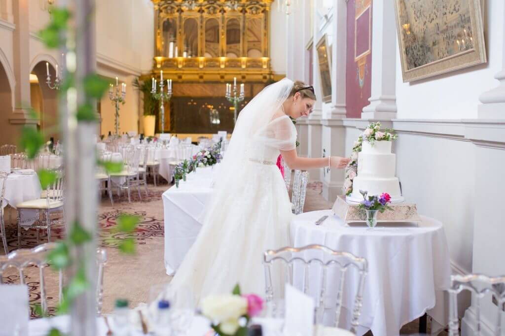 37 bride checks decorative cake before dinner reception de vere beaumont estate venue windsor berkshire oxfordshire wedding photography