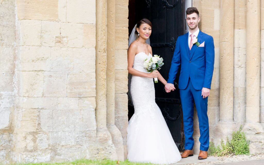bride floral bouquet groom posed traditional family portrait after marriage ceremony iffley village church oxford oxfordshire 12