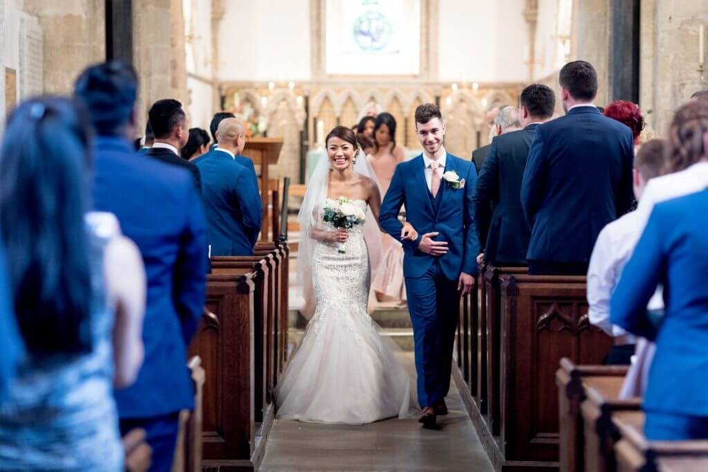 bride groom bridesmaids walk down aisle after marriage ceremony by vicar iffley village church oxford oxfordshire wedding photography 10