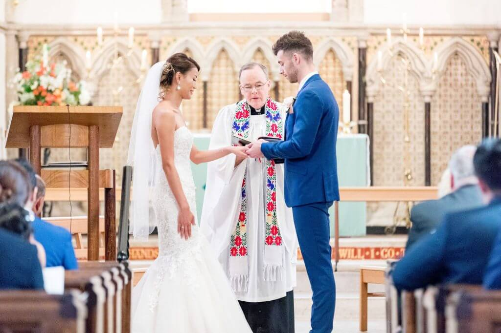 bride groom exchange rings marriage ceremony by vicar iffley village church oxford oxfordshire wedding photography 09