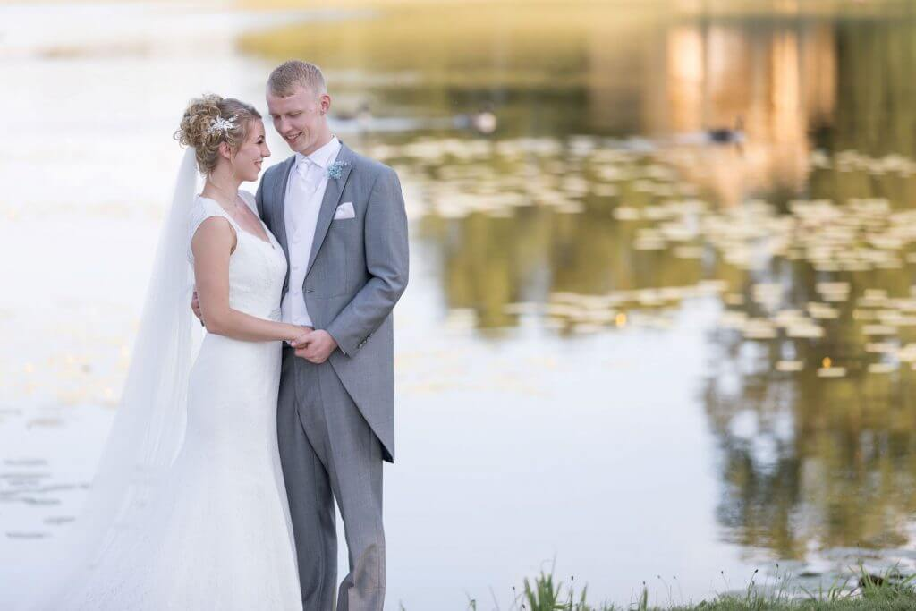 bride groom formal dress suite pose by lake for traditional family portrait stowe house buckinghamshire venue oxfordshire wedding photography 20