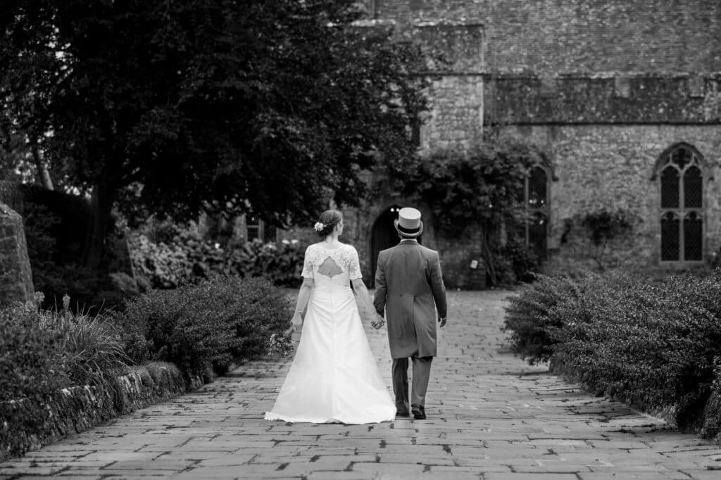 bride white dress groom top hat formal grey dress suite walk in churchyard after marriage ceremony oxfordshire wedding photography 48