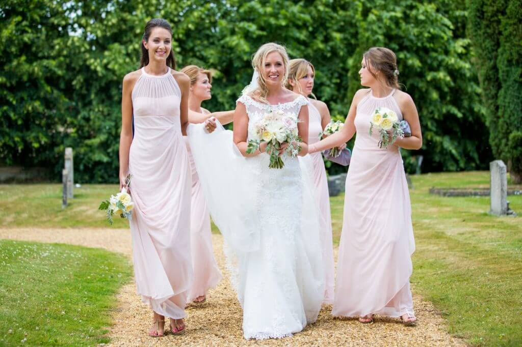 bride white dress with flowers bouquet bridesmaids pink dresses walk in churchyard before marriage ceremony oxfordshire wedding photography 51