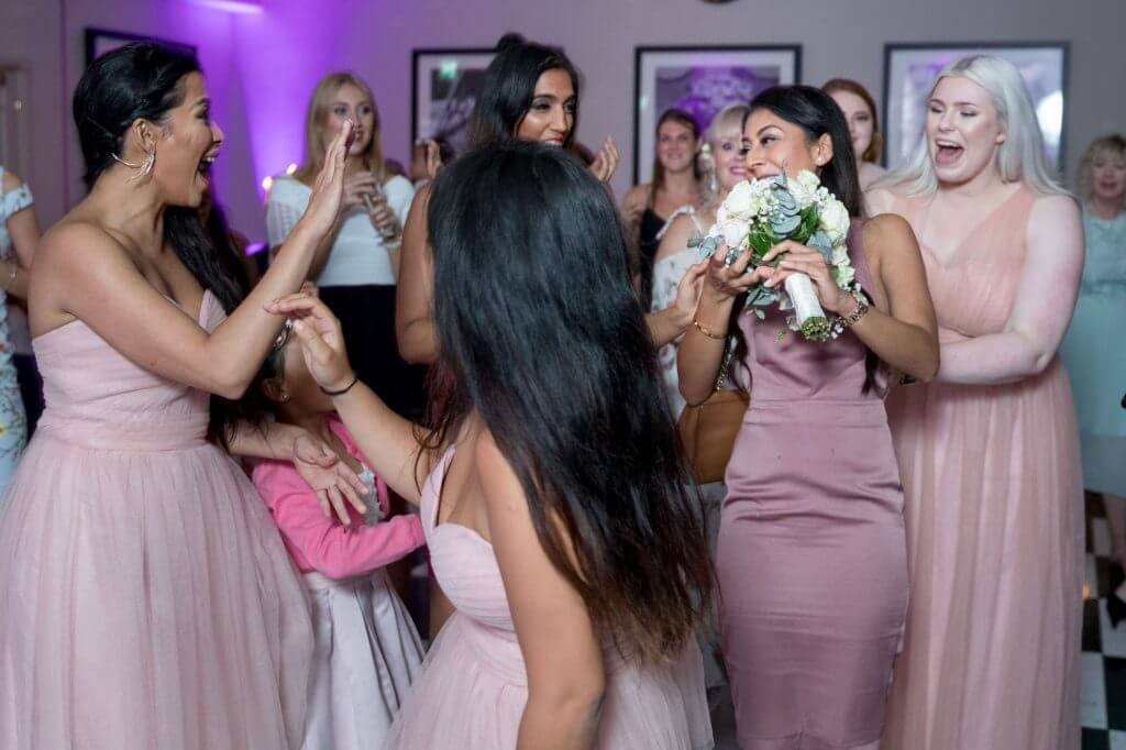 brides floral bouquet caught bridesmaid in pink dresses watch evening party celebration milton hill house venue steventon abingdon oxford oxfordshire wedding photography 46