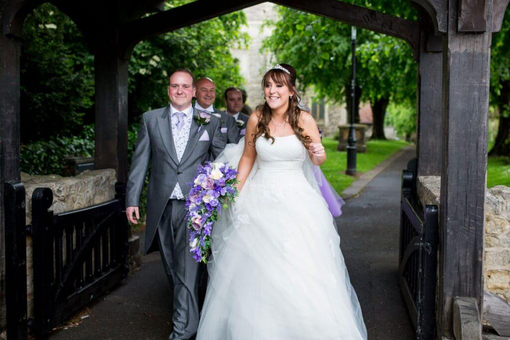just married bride blue floral bouquet groom grey morning suit walk through churchyard gate after church marriage ceremony oxfordshire wedding photographer 49