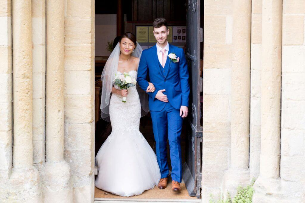 just married bride groom following ceremony by vicar iffley village church oxford oxfordshire wedding photographer 11