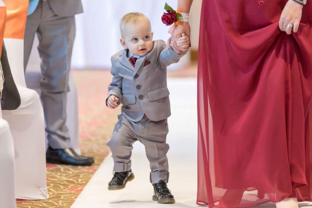 page boy walking down aisle with bridesmaid marriage ceremony hellidon lakes venue northamptonshire oxfordshire wedding photography 55