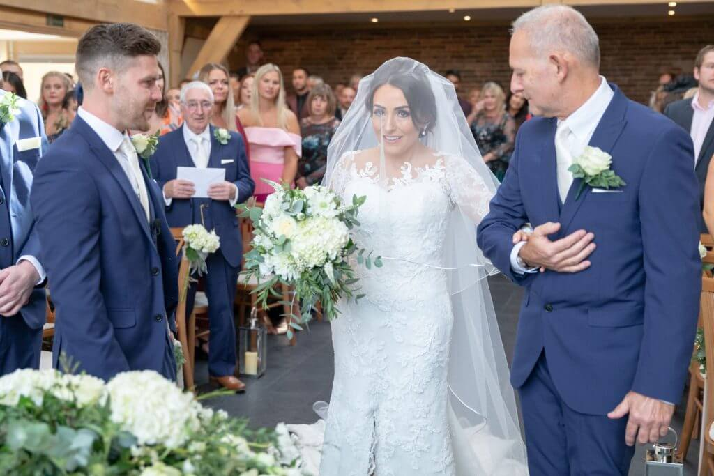 bride with bouquet and groom at the alter mythe barn luxury venue leicestershire oxford wedding photography