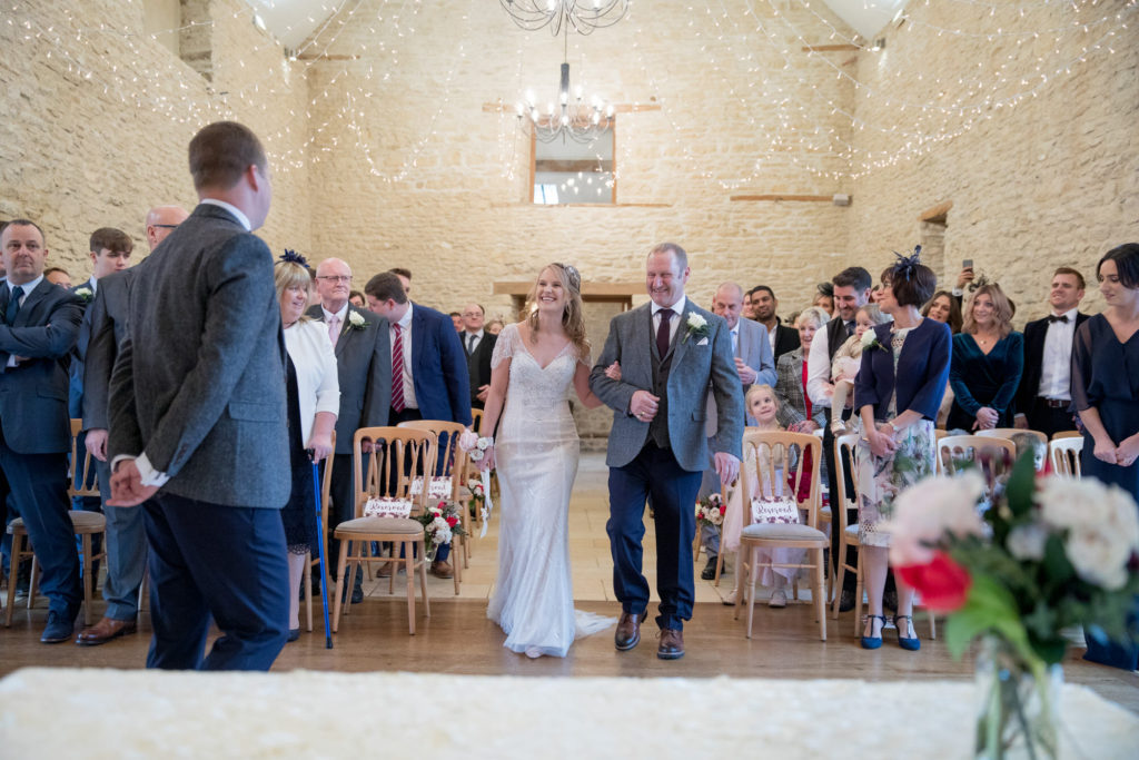 bride and father walk down aisle kingscote barn oxford wedding photographer