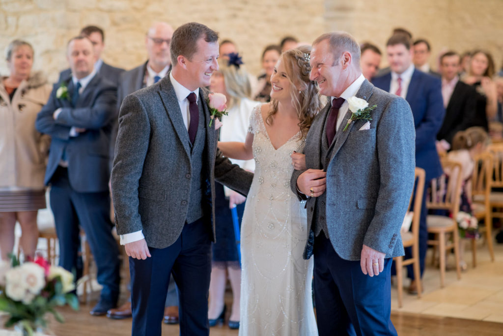 smiling bride groom and father wedding ceremony kingscote barn oxford wedding photographer