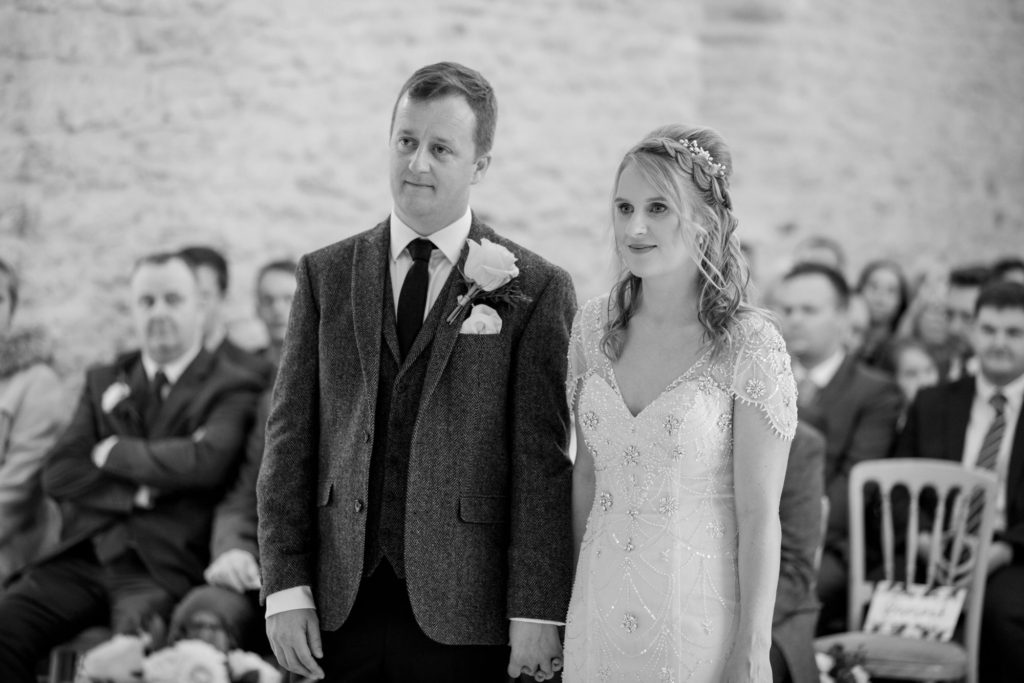 bride groom at alter kingscote barn tetbury oxfordshire wedding photographer