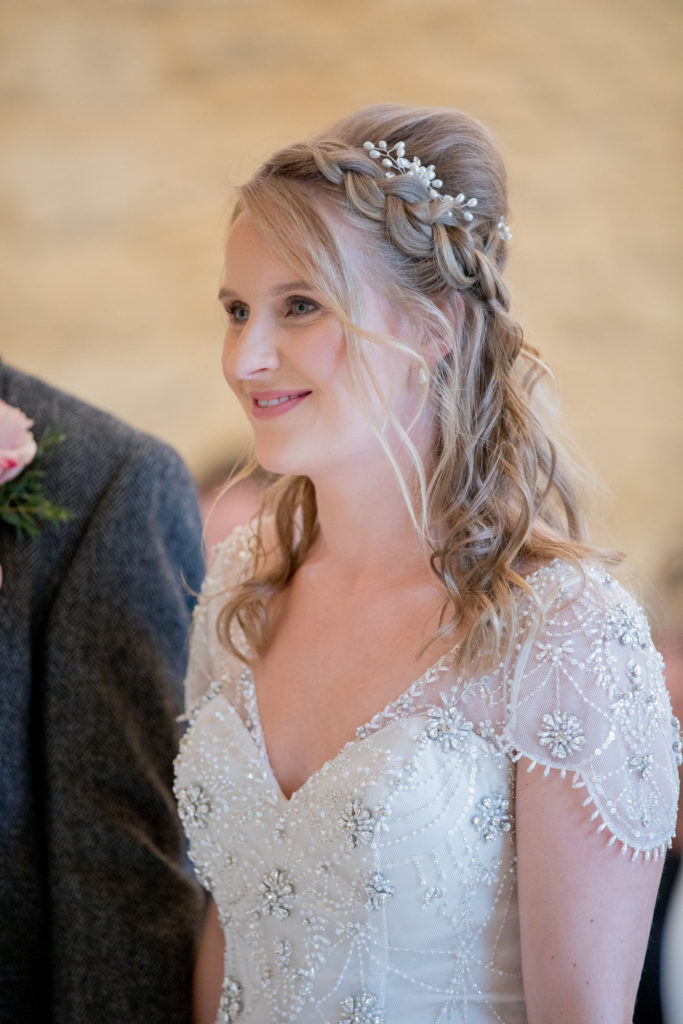 smiling bride at alter kingscote barn tetbury oxford wedding photographer