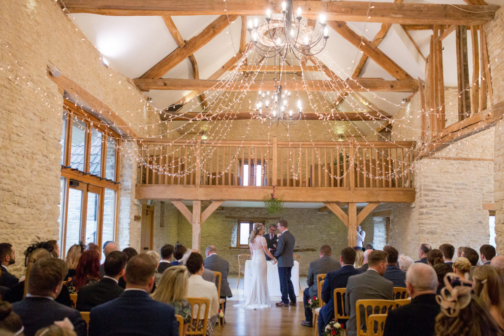 bride groom under minstrel gallery kingscote barn tetbury oxford wedding photographer