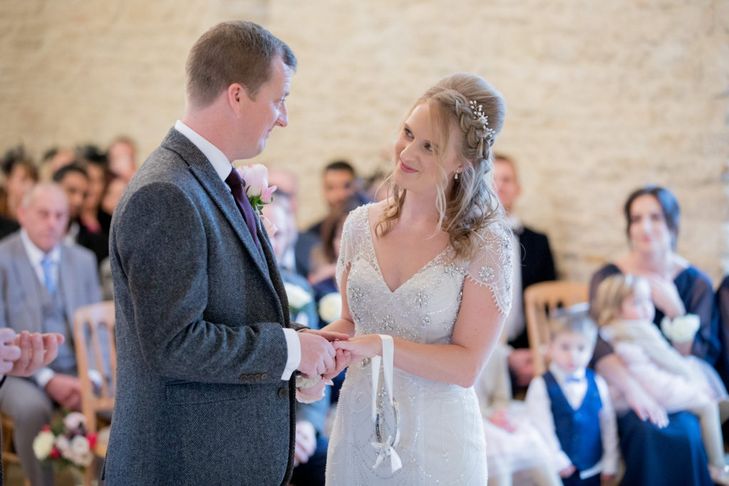groom puts ring on bride kingscote barn tetbury oxfordshire wedding photography