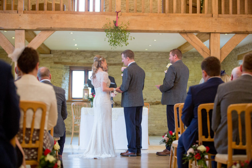 bride groom under miseltoe during ceremony kingscote barn oxfordshire wedding photographer