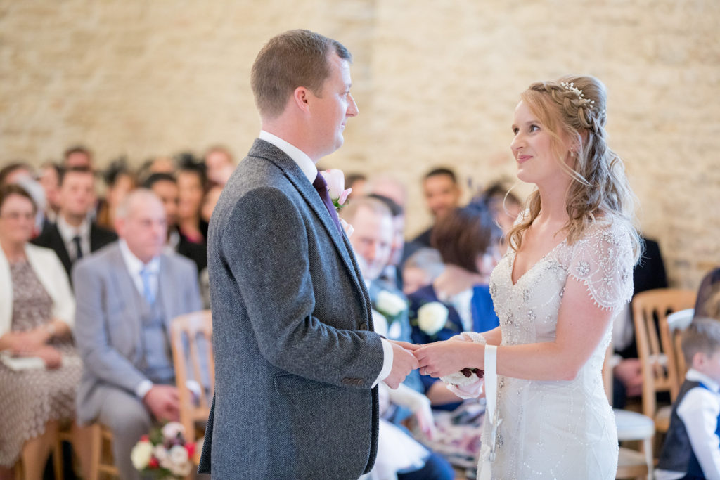 bride looks lovingly at groom kingscote barn ceremony oxford wedding photographer