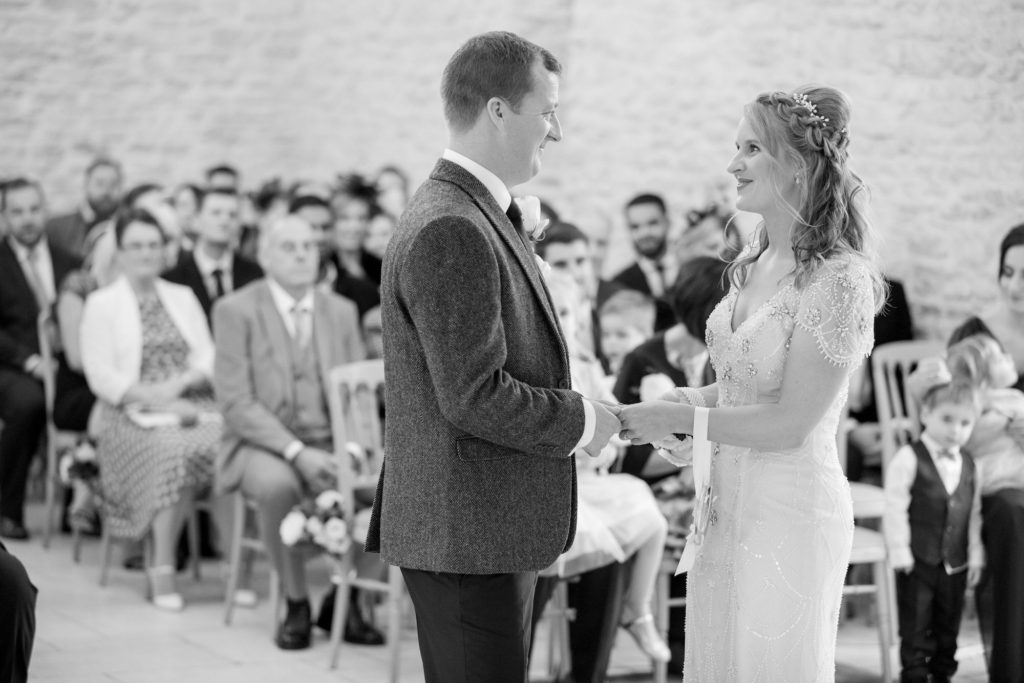 smiling bride groom at alter kingscote barn ceremony oxford wedding photography