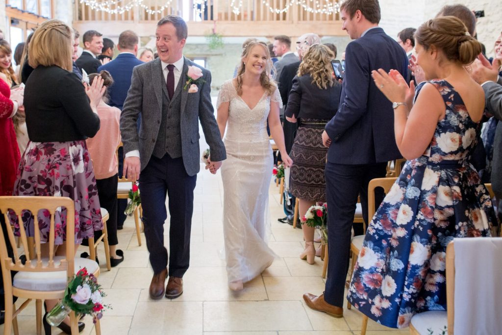 laughing groom with bride walk down aisle kingscote barn oxford wedding photographer