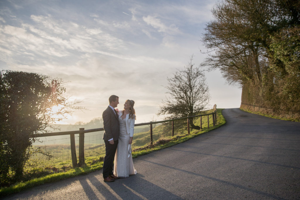 bride groom on country road at sunset kingscote barn tetbury oxford wedding photographer