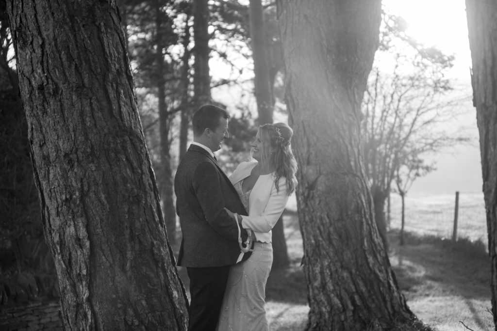 bride groom embrace under trees kingscote barn tetbury oxford wedding photographer