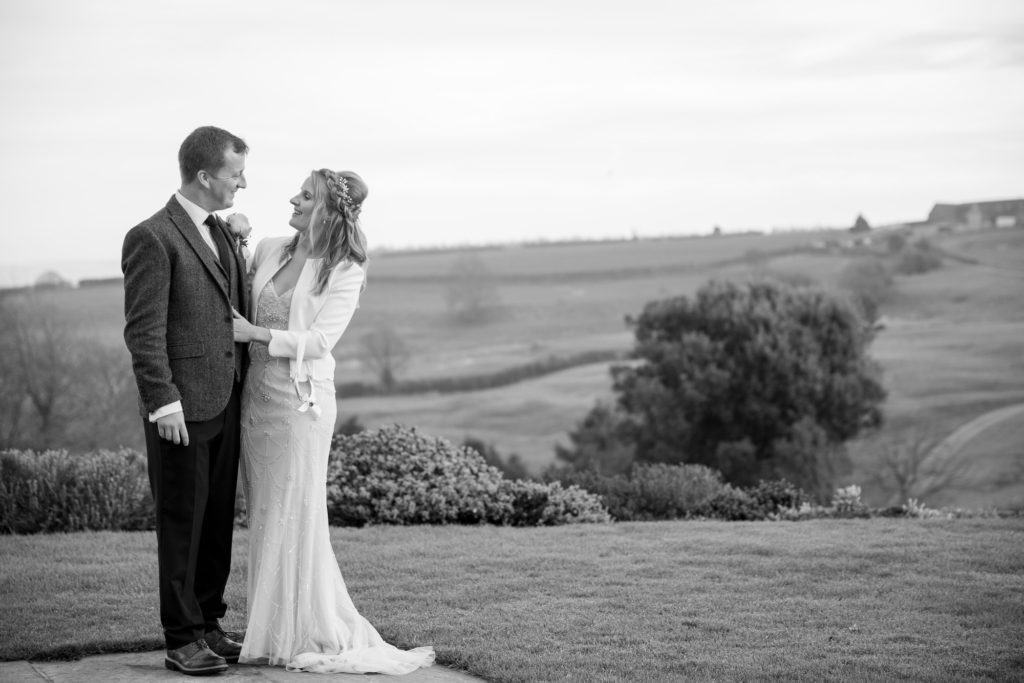 bride groom embrace rolling countryside backdrop kingscote barn oxford wedding photography