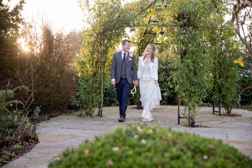 bride groom stroll under pergoda kingscote barn gardens oxford wedding photographer