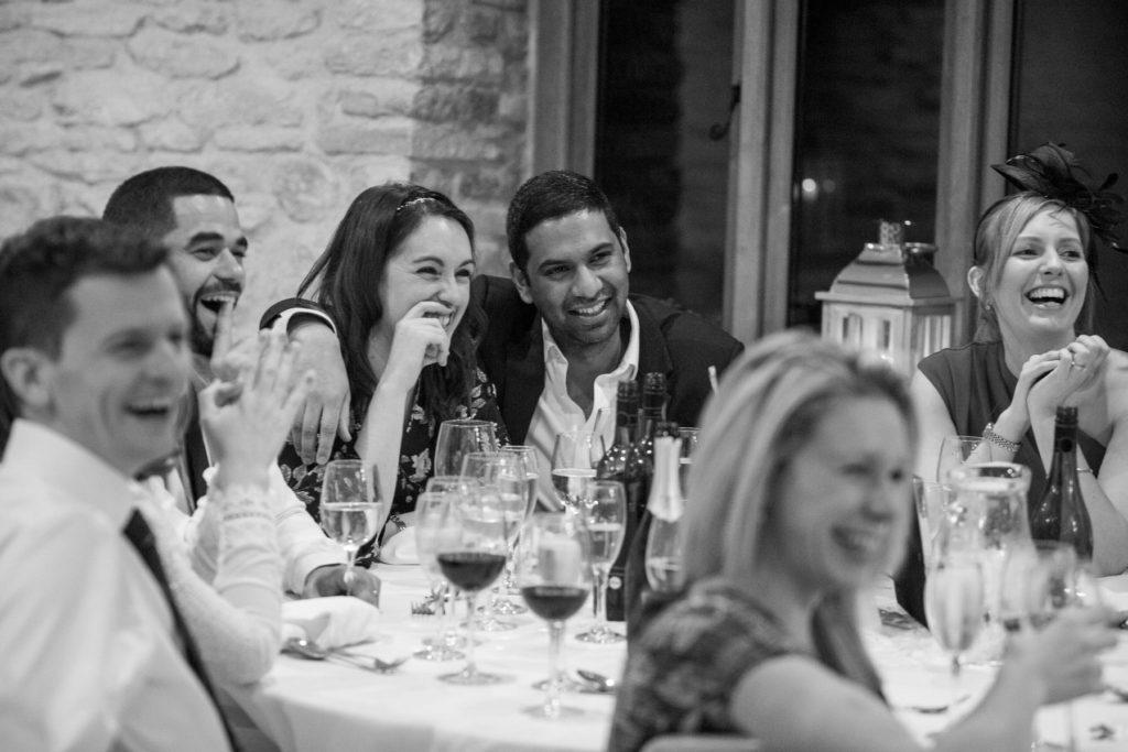 laughing friends dinner reception kingscote barn tetbury oxfordshire wedding photographer