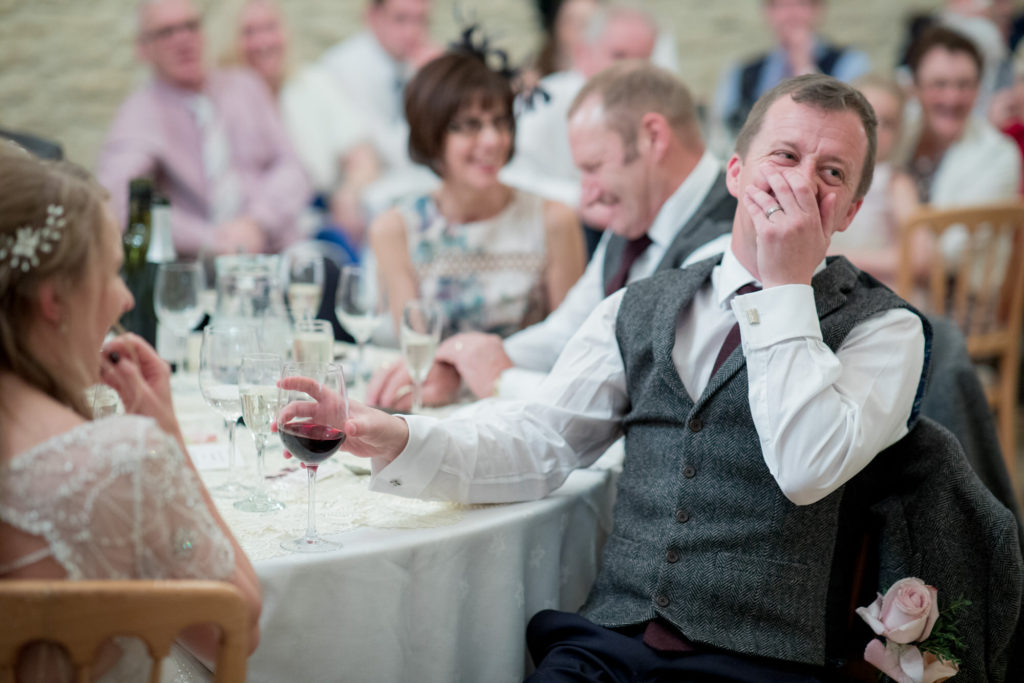 groom laughs at speeches kingscote barn reception tetbury oxfordshire wedding photography