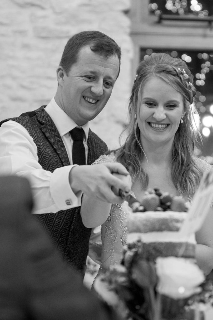 smiling bride groom cut cake kingscote barn reception tetbury oxford wedding photographer